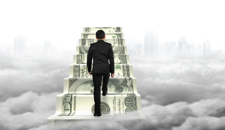 man in business attire stepping on giant dollar bills floating above clouds