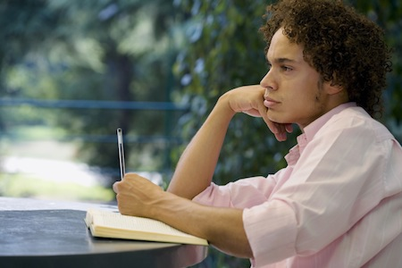 man in deep thought with book and pen